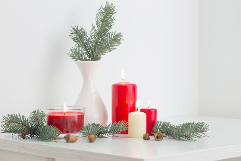 Déco noel DIY avec bougies rouges et branches de sapin dans un vase blanc.