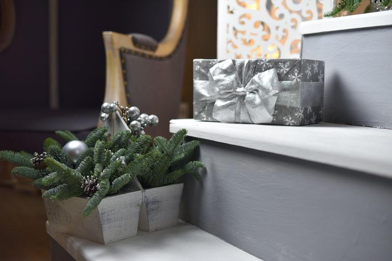 Pots décorés avec branches de sapin, pommes de pin et boules de Noël argentées.