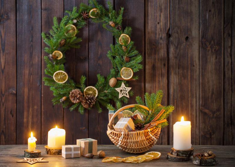 Couronne de Noël réalisée avec branches de sapin, fruits secs et de pommes de pin.