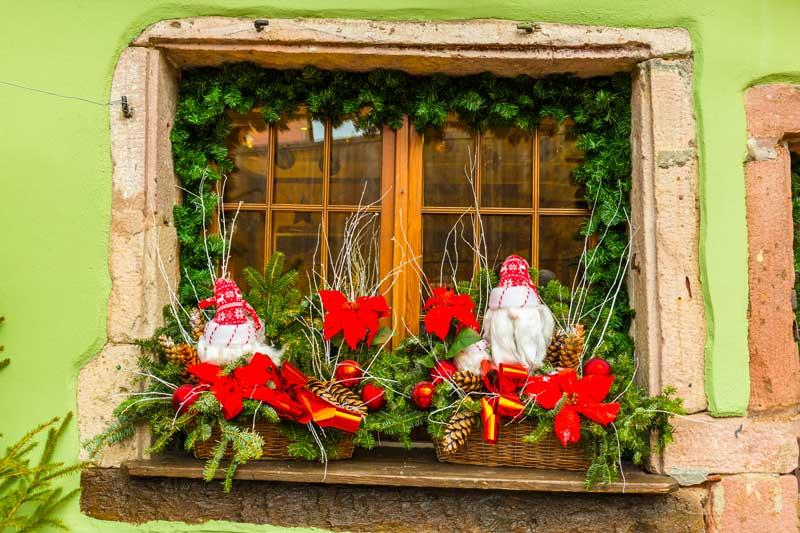 Fenêtre décorée avec guirlande, composition avec branches et pommes de pin, idéal pour Noël.
