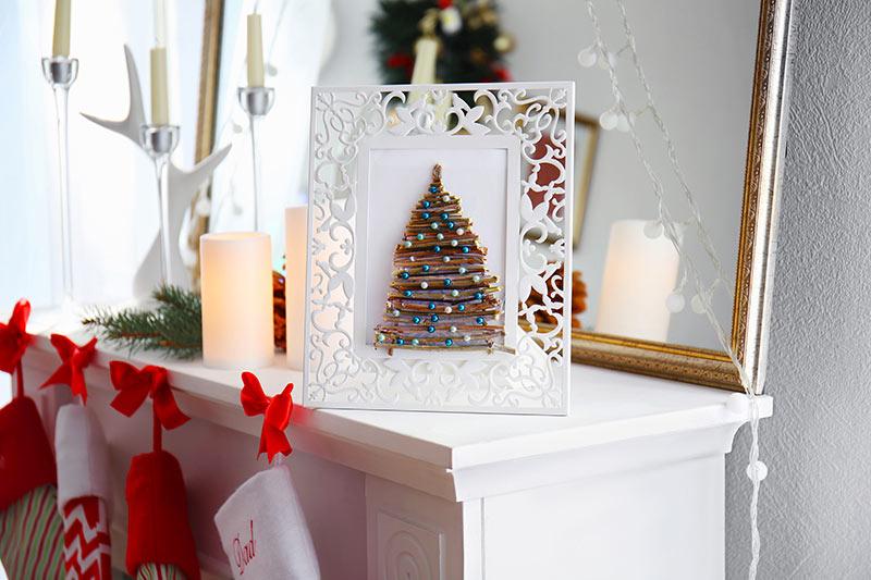 Petit sapin de Noël réaliser avec brindilles dans un cadre photo.