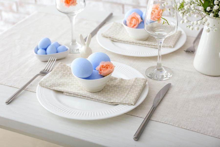 Tavola di Pasqua Shabby con ciotole bianche e ovetti blu pastello.