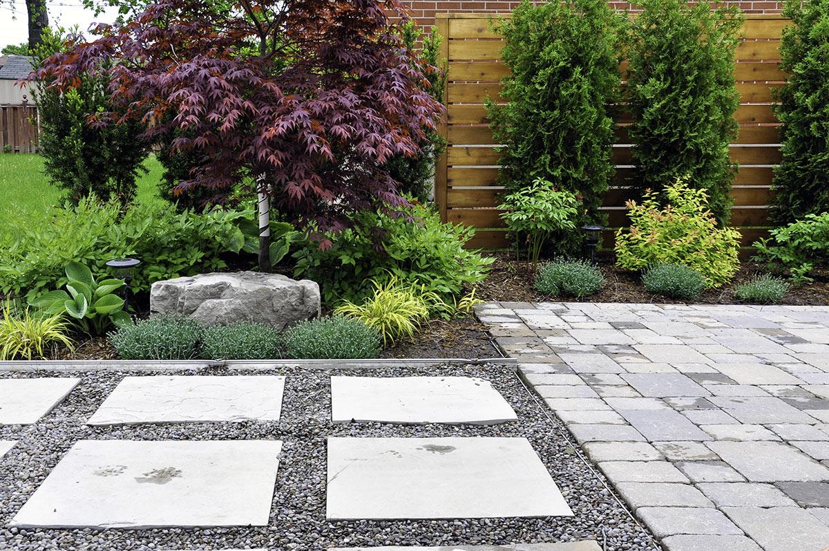 Allée de jardin réalisée avec des dalles en pierre.