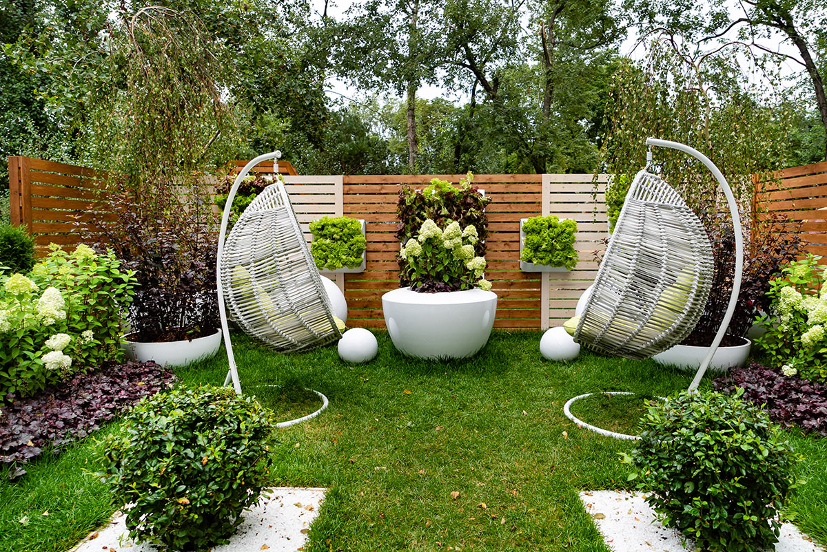 petit jardin avec clôture en bois, 2 sièges d'extérieur et décorations de plantes.