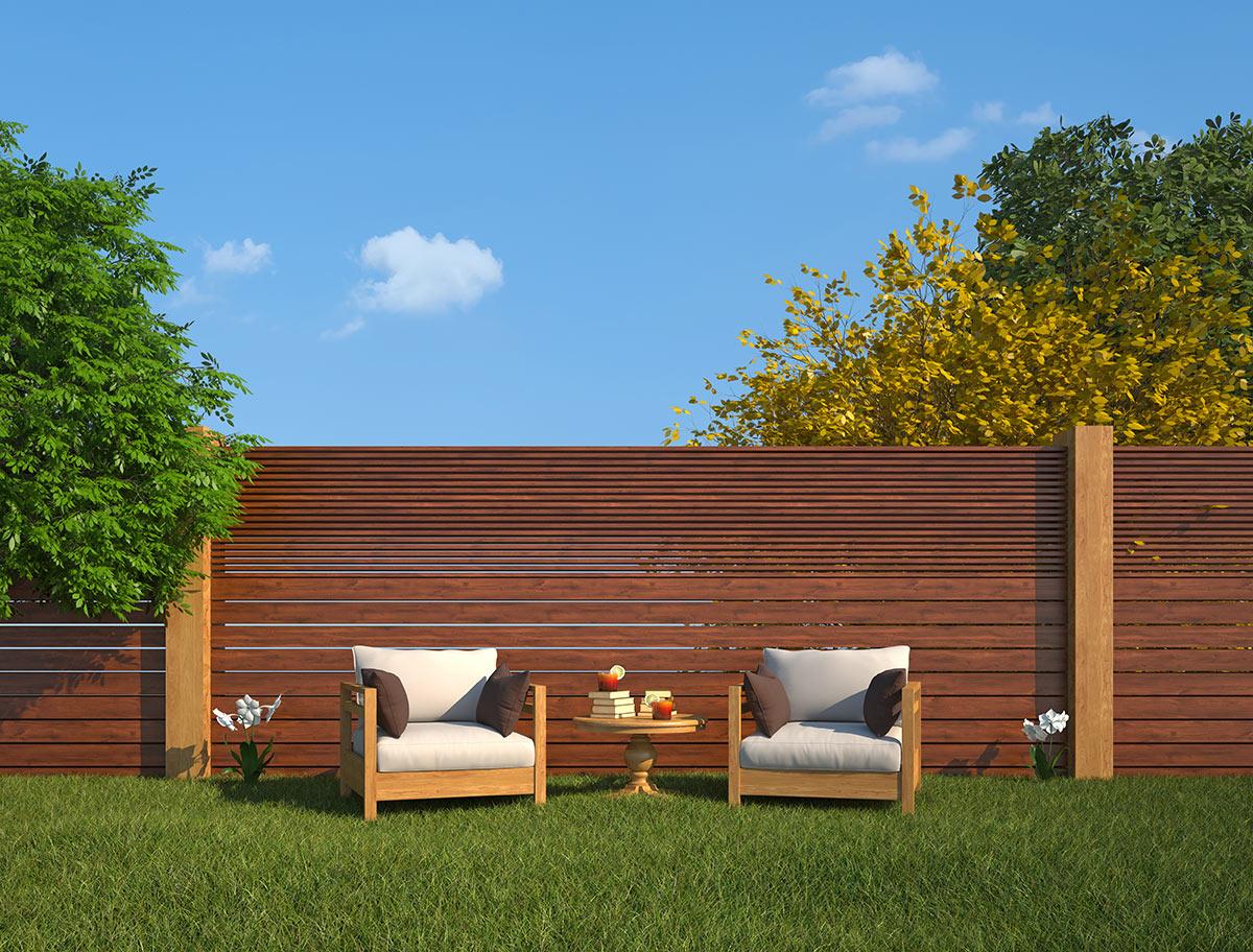 grande clôture de jardin en bois avec planches orizontales, 2 fauteuils d'extérieur avec table basse.