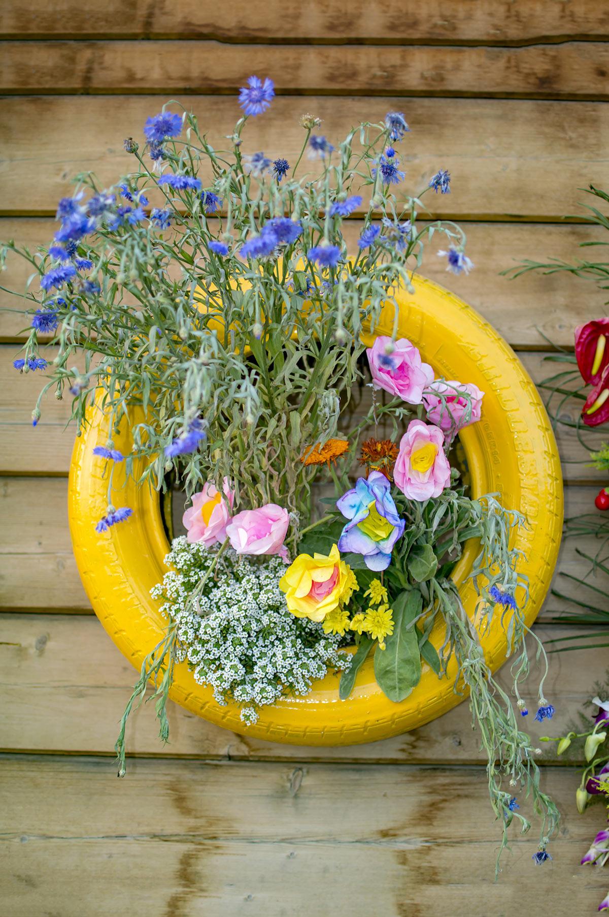 vieu pneu jaune avec fleurs dans le jardin