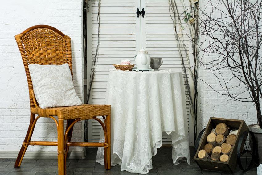 petit salon shabby avec chaise marron en osier et coussins blancs brodés