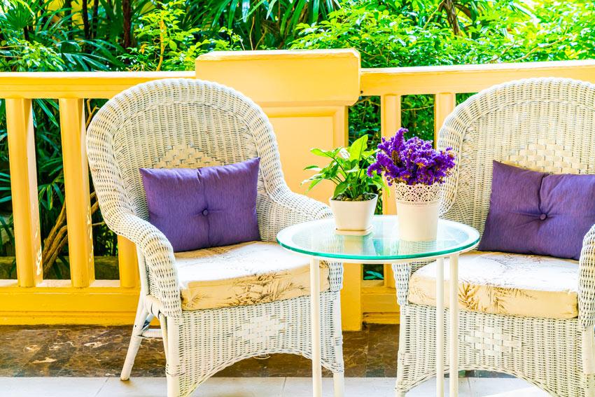 salon shabby avec deux chaises blanches en rotin et coussins violets