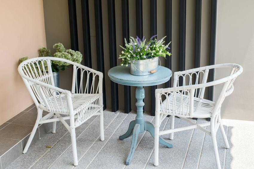 terrasse décorée en style shabby chic avec deux chaises en osier et une petite table