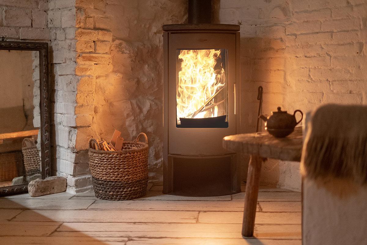 salon avec cheminée et panier en osier pour ranger le bois.