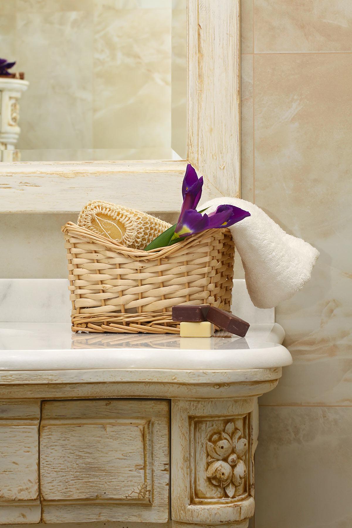 meuble de salle de bain avec beau panier en osier pour ranger savon et serviettes.