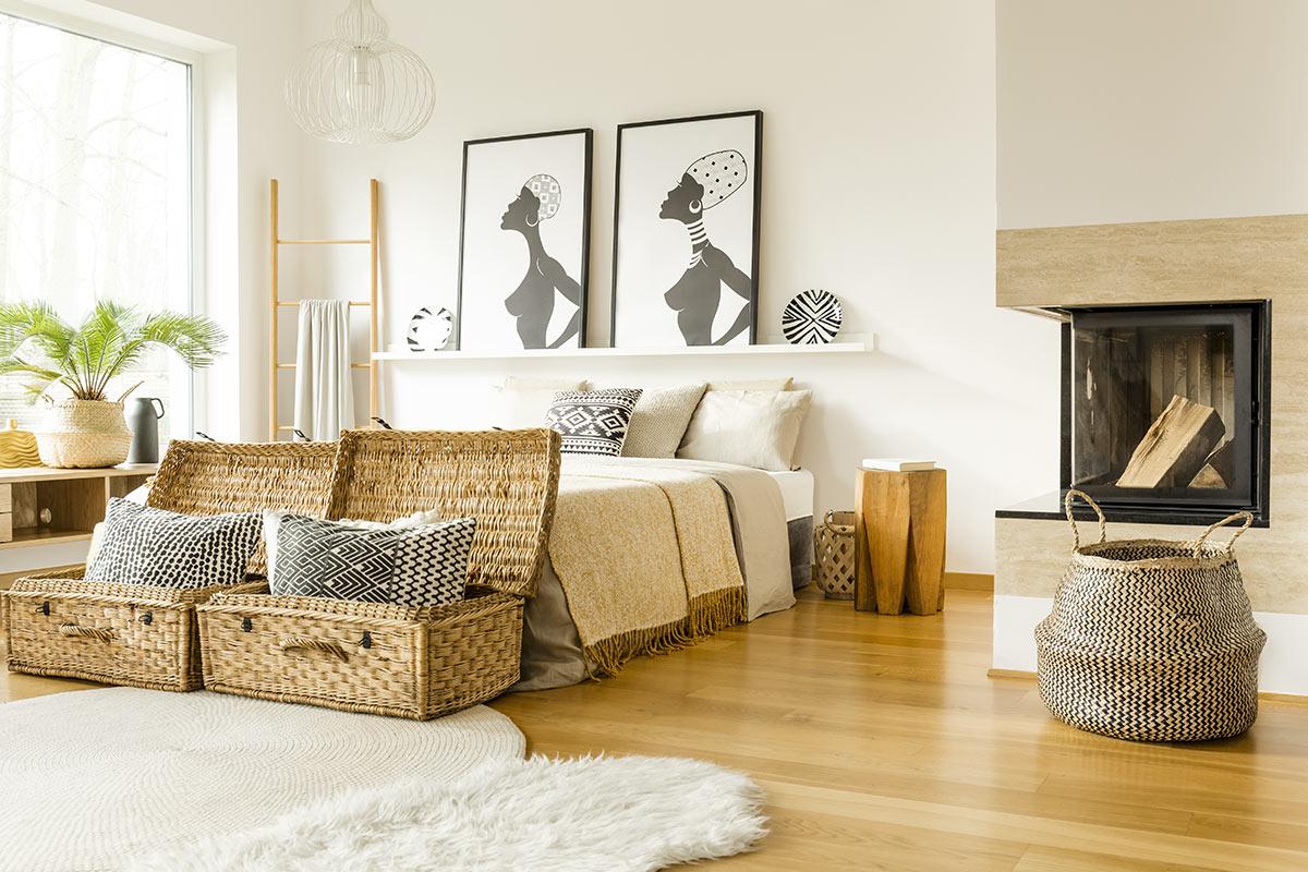 Chambre moderne avec tableaux africains et deux beaux paniers en osier au pied du lit.