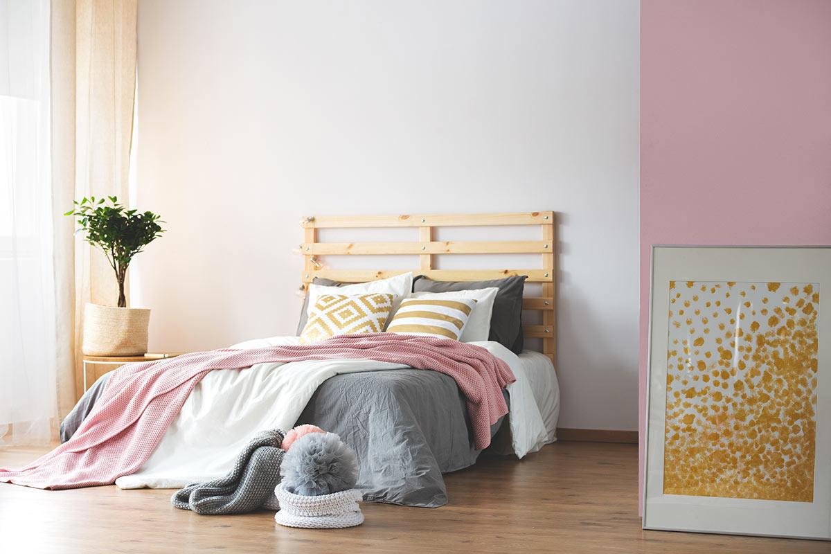 tête de lit DIY avec palettes dan dcette chambre avec mur blanc et rose