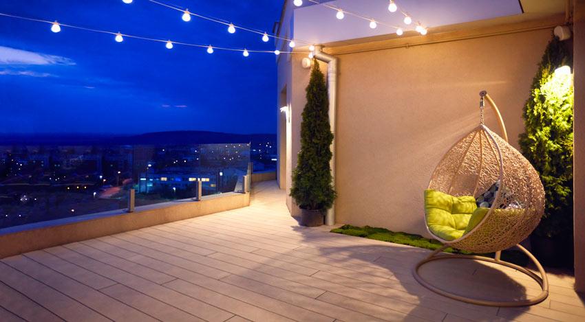 terrasse illuminée avec des lampes suspendues à un fil
