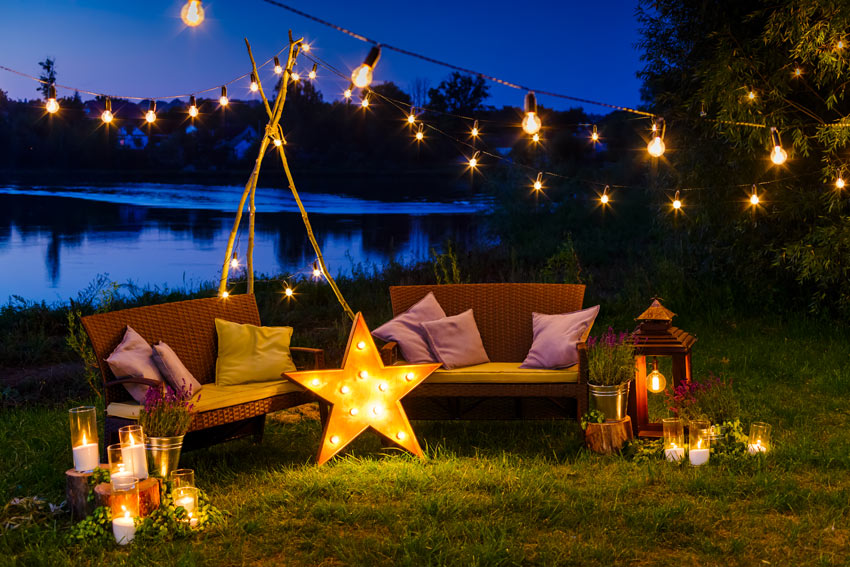 jardin illuminé avec lampes en forme d'étoile et ampoules suspendues à un fil