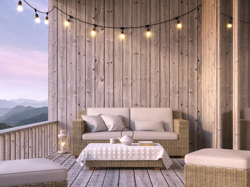 balcon avec canapé et lumières suspendues à un fil