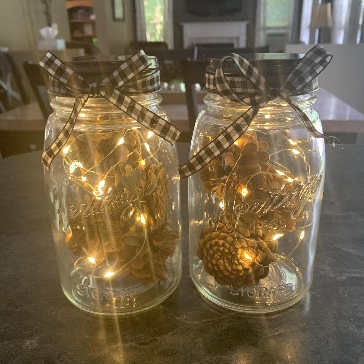 Lanterne fait maison avec bocaux en verre, pomme de pin e guirlande lumineuse.